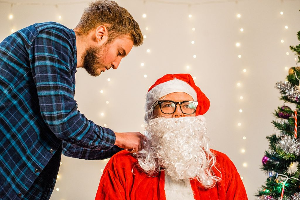 Alan Carr dressed as Santa with production assistant making an adjustment