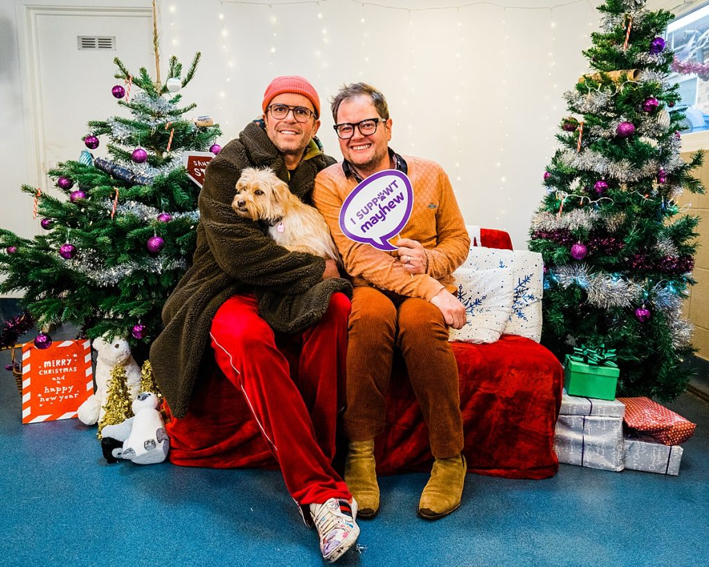 """Charity Photography - Alan Carr and husband pose with their dog holding sign reading """"I suppawt Mayhew"""""""