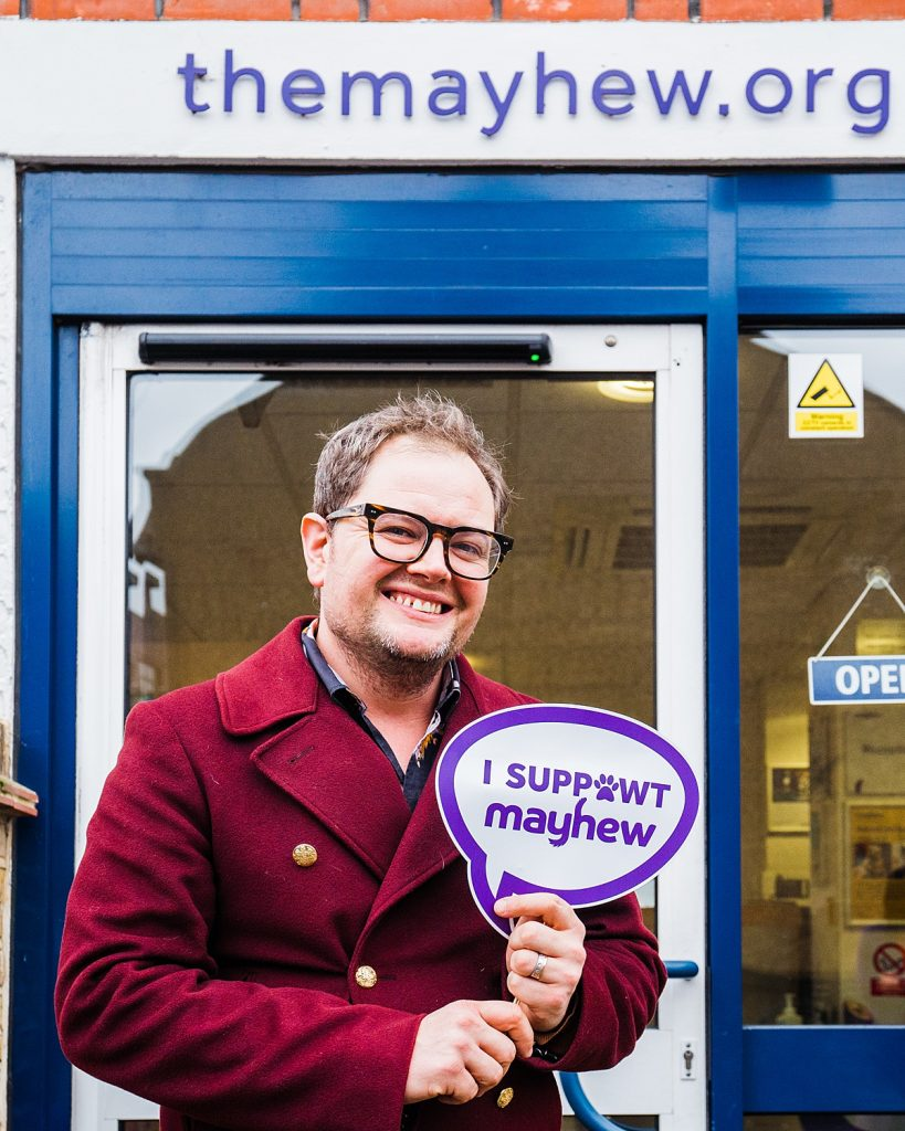 """Charity Photography - comedian Alan Carr stands outside Mayhew with a sign reading """"I suppawt Mayhew"""""""